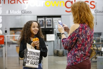 An adult takes a photo of a child holding an orange and yellow Make Your Own Glass pumpkin at The Studio. The child is smiling and holding the glass pumpkin close to their face.
