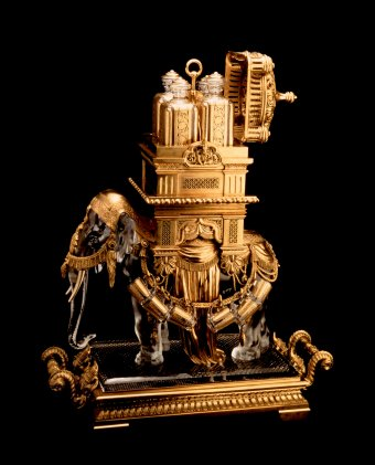 Fig. 3: Liqueur cabinet in the shape of an elephant with a howdah, pressed, etched, cut, gilded; gilded bronze. Made for the Baccarat display at the 1878 world's fair in Paris. H. 65 cm, L. 58 cm. Four carafes fit inside the palanquin, and 12 mugs hang from the bronze harness. The Crillon Palace, Paris.