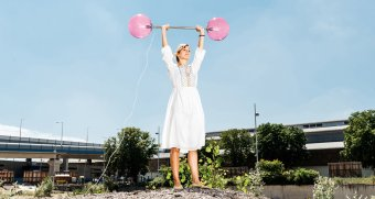 A woman in a white sundress proudly holds up Super Strong Lamp, which mimics a barbell