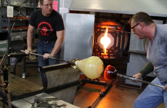 Gaffer George Kennard works with designer Sigga Heimis in a GlassLab session in Corning, May 2012