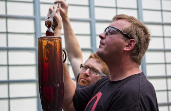 Gaffers George Kennard and Dane Jack work with Masamichi Udagawa and Sigi Moeslinger at GlassLab in Corning