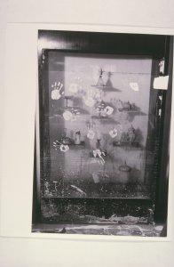 [Muddy handprints on flood-damaged gallery case with Venetian glass vessels] [slide].