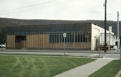 [Exterior view of the Acme building and the freezer trailer] [slide].