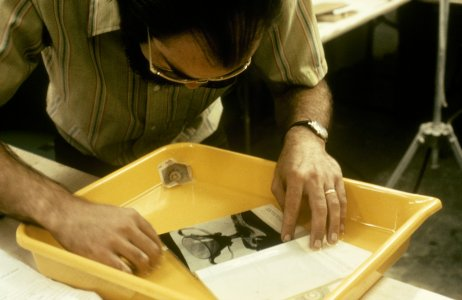 [Library volunteer soaks book page in deacidification solution] [slide].