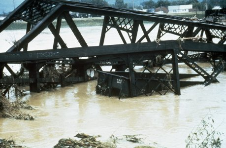 [Floodwaters sweep railcars filled with coal into the river] [slide].