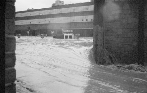 [Flood water behind factory building] [picture].
