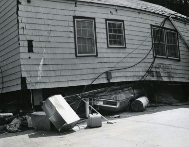 [A home swept away by floodwaters came to rest upon a car] [picture].