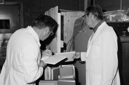 [Two men in white lab coats examining books] [picture].
