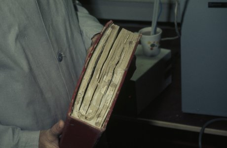 [Flood-damaged book covered with mud] [slide].