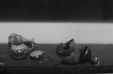 [Flood-damaged glass objects in a gallery case covered with mud] [picture].
