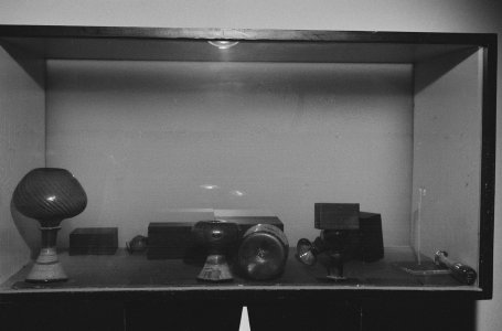 [Glass objects tipped over and upside down in gallery case] [picture].