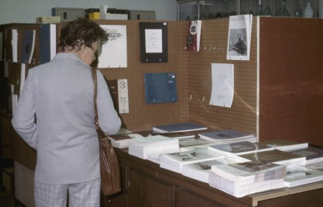 CMG Seminar, Oct. 6-8, 1977 [slide]: [An unidentified woman looks at books for sale].