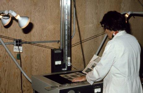 [Library volunteer microfilming trade catalog] [slide].