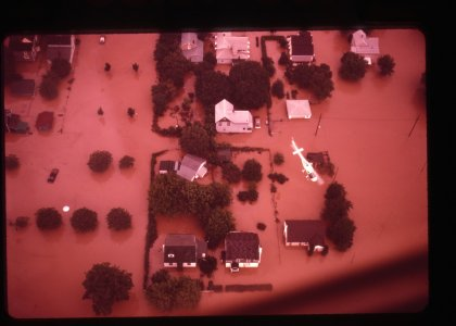 [Aerial view of flooded neighborhood and helicopter searching for survivors] [slide].