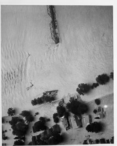 [Aerial view of destroyed railroad bridge and flooded neighborhood along the dike] [slide].