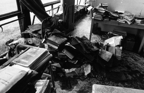 [Flood-damaged museum office with books stacked ready to transport to freezer] [slide].