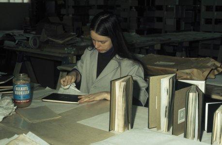 [Library volunteer cleaning restored book cover] [slide].