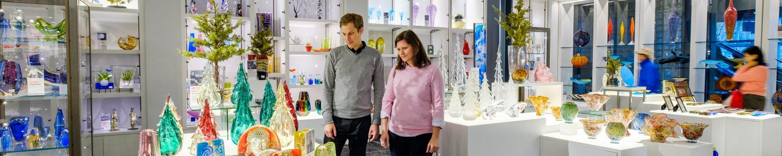 A man and woman look at glass art in a museum gift shop