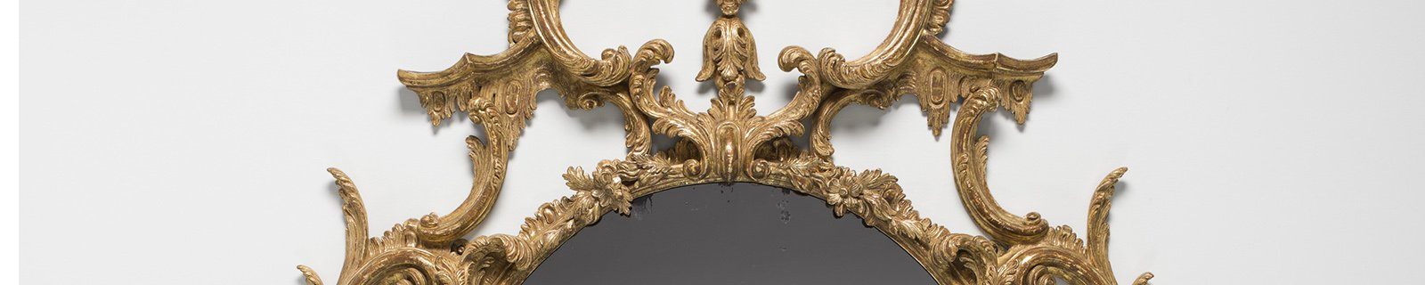 A cropped view of a mirror with an elaborate gold frame with swirls.