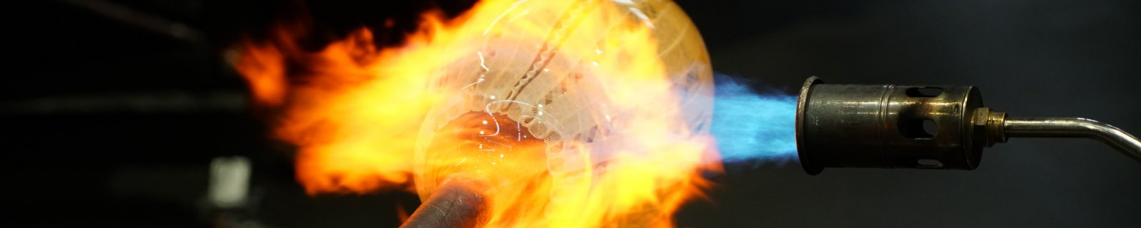 A close up of a torch enveloping a blown sphere of clear and white molten glass