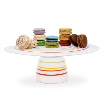 White and rainbow striped glass dessert stand with multiple colors of Macaron cookies on top