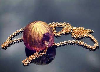 engraved pink and gold round pendant on a gold chain