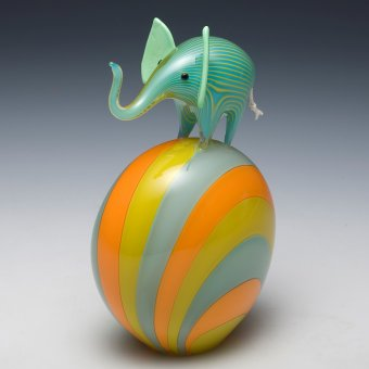 Colorful blown glass sculpture of an elephant on an oblong sphere.