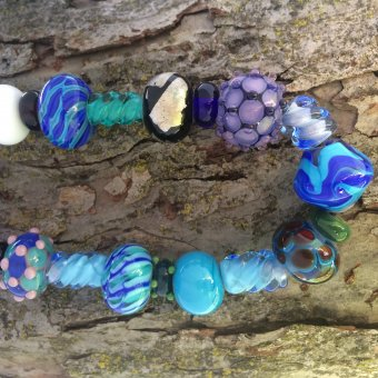 String of blue, indigo, and violet flameworked glass beads.