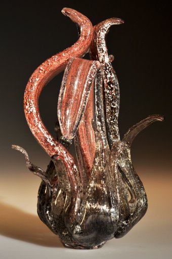 A black and red glass sculpture with non-glass inclusions