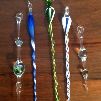 Five colorful flameworked icicles in shades of blue, green, and clear glass