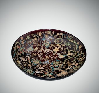 A brown bowl from the Roman Empire with a detailed inlaid scene of ducks and plants in tan, blue, and green
