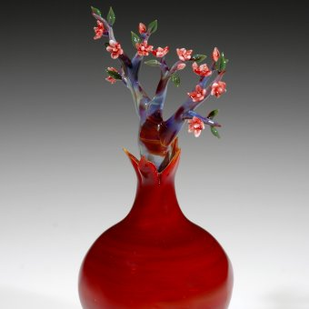 Red glass vase with glass tree and pink flowers