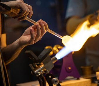 A close up of an artist's hands as they use a torch to melt a a yellow circle of class on a clear rod of glass