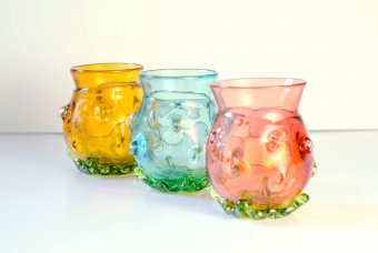 Three colored glass tumblers in pink, blue, and yellow