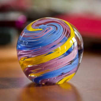 Blue, violet, and yellow spherical glass paperweight.