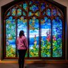 A woman stands in front of a large stained glass window, looking into its colorful nature design.