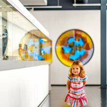 A small child smiles as she walks through the Contemporary Glass gallery.