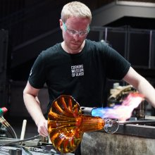 A glassblower heats a vase using a handheld torch.