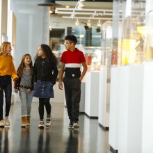 Group of kids of various ages walking in the Contemporary Glass gallery with white cases.