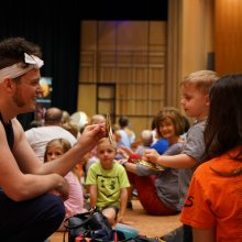 A toddler engages with a performer using a small cymbal.