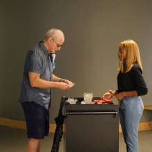 A visitors holds a piece of cut glass while a volunteer stands behind the relevant cart.