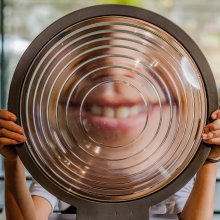 A child's smile is seen distorted by glass in the Optics gallery.