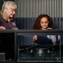 A smiling child breaks glass during the Glass Breaking demonstration as the demonstrator looks on.