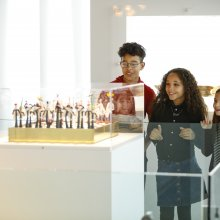 A group of children at various ages smile as they look a glass chess set.