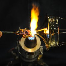 A close up as a detail on the top of a glass lid is held in a flame.