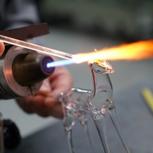 A transparent, hollow glass deer is created using a concentrated flame.