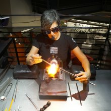 Pictured from a high angle, a flameworker uses two rods of transparent glass and flame to form a small sculpture.