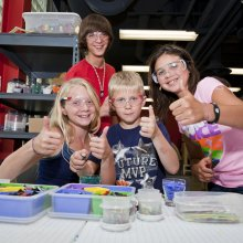 Three children and one volunteer smile and give thumbs up, with tools for the fusing Make Your Own Glass project in front of them.