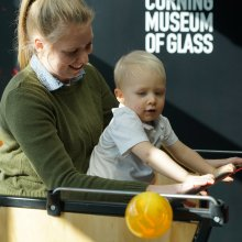 An adult smiles as they hold a toddler pushing a blowpipe in an interactive display.