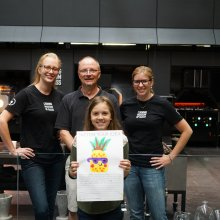 A child smiles as she holds her winning design. Three glassblowers smile behind her.